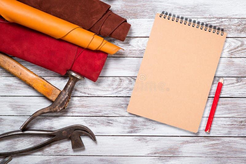 El cuero brillantemente coloreado en los rollos, herramientas de funcionamiento, zapato dura, cuaderno con el lápiz en el fondo b imágenes de archivo libres de regalías