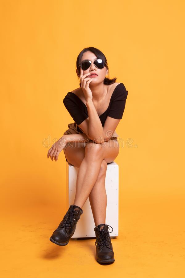 El cuerpo completo de la mujer asi?tica joven hermosa se sienta en silla foto de archivo