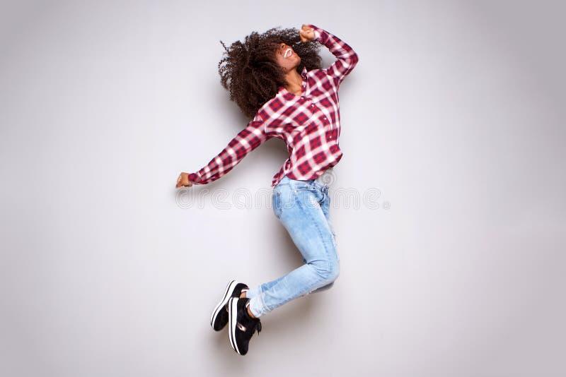 El cuerpo completo excitó a la mujer joven que saltaba en aire contra el fondo blanco fotografía de archivo