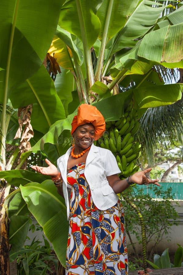 El cuerpo completo vertical de una mujer afroamericana alegre actitudes nacionales coloridas brillantes de un vestido que llevan foto de archivo libre de regalías