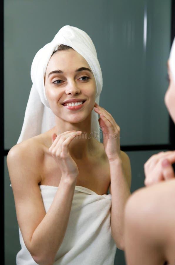 El cuidar de la mujer de su piel en el cuarto de baño fotos de archivo libres de regalías
