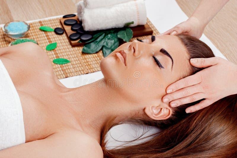 El cuidar en exceso y masaje para la cara hermosa de la mujer joven en salón del balneario – dentro, masajista que hace masaje en imagen de archivo