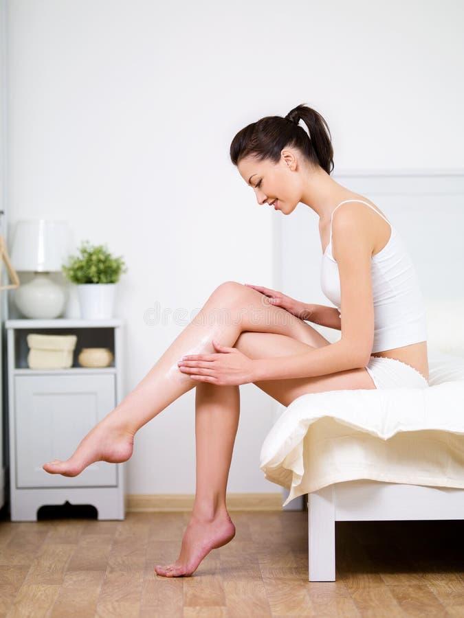 El cuidar sobre la pierna de la mujer con crema fotografía de archivo