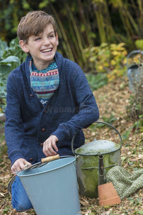 El cultivar un huerto feliz del niño masculino del muchacho imagen de archivo