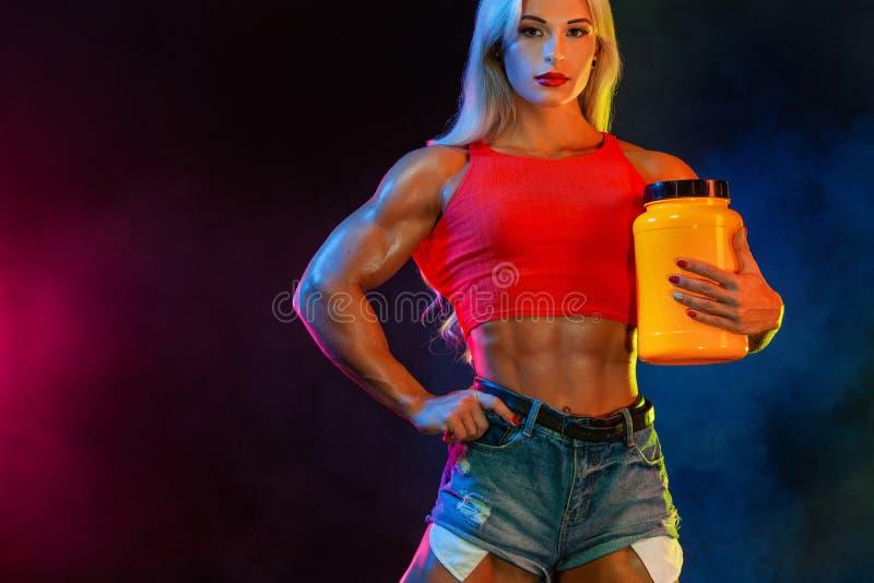El culturista atlético de la mujer joven en los esteroides sabe cuantas veces puede usted tener una comida del tramposo fotos de archivo libres de regalías