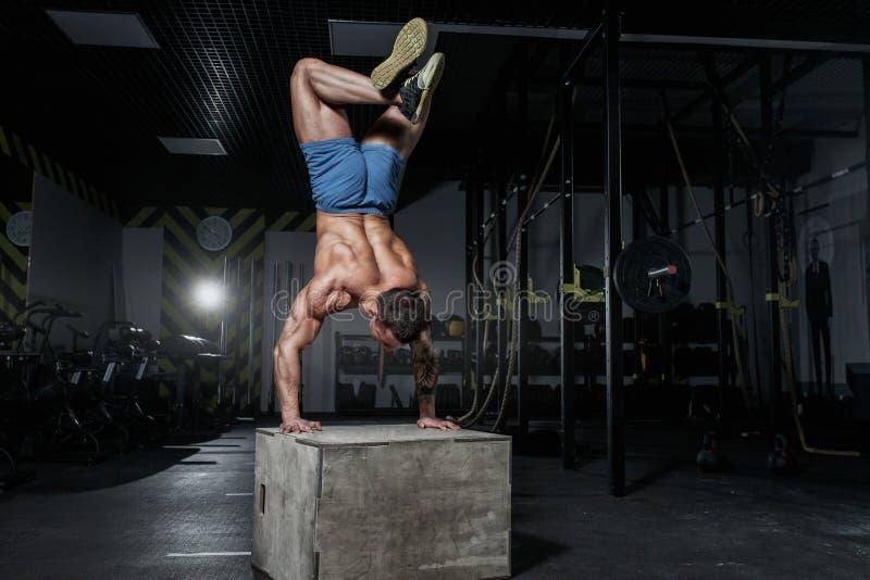El culturista atlético del hombre bombeado se coloca en sus manos en gimnasio imagenes de archivo