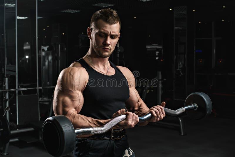 El culturista atlético fuerte brutal de los hombres entrena en el gimnasio imagenes de archivo