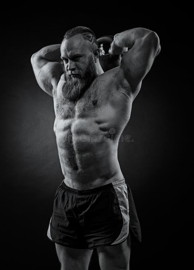 El culturista con una barba levanta un kettlebell pesado imagen de archivo