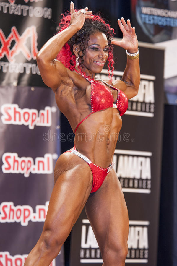 El culturista femenino en bíceps doble delantero presenta y bikini rojo fotografía de archivo