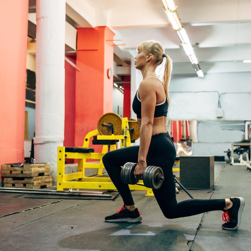 El culturista hermoso de la muchacha, ejecuta ejercicio con pesas de gimnasia foto de archivo