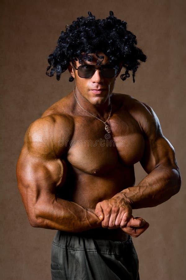 El culturista muscular con el pelo rizado muestra su bíceps imagen de archivo