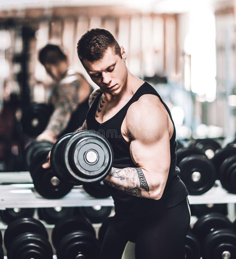 El culturista realiza ejercicios con pesas de gimnasia Foto con el espacio de la copia fotos de archivo