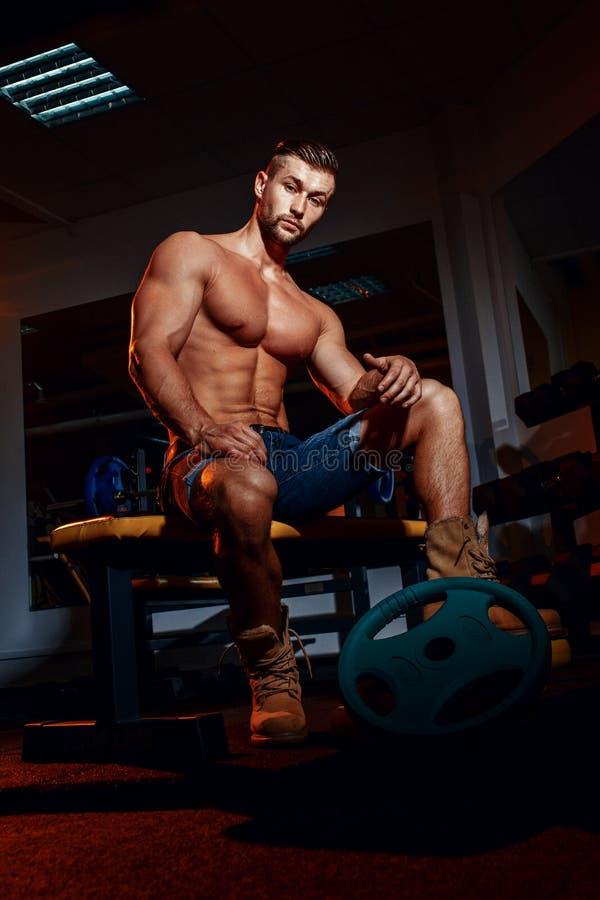 El culturista se sienta en un banco de peso, él toma una rotura Hombre muscular en un lugar del entrenamiento en un gimnasio y so imagen de archivo