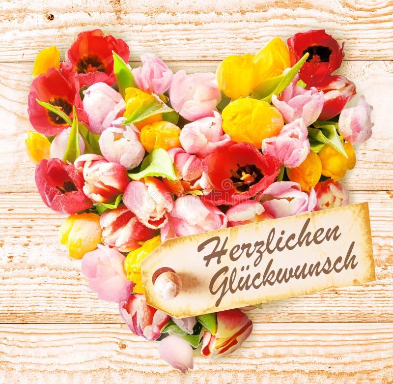 El cumpleaños alemán desea en un corazón floral colorido fotografía de archivo