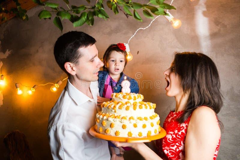 El cumpleaños de los niños del día de fiesta de la familia del tema y soplar hacia fuera velas en la torta grande familia joven d imagen de archivo libre de regalías