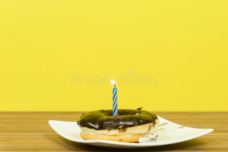 El cumpleaños del buñuelo mira al trasluz feliz cumpleaños con un fondo amarillo fotografía de archivo libre de regalías