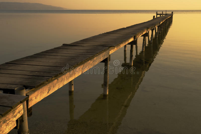El día acaba, los rayos pasados del sol ilumina el embarcadero de madera largo en el lago fotografía de archivo
