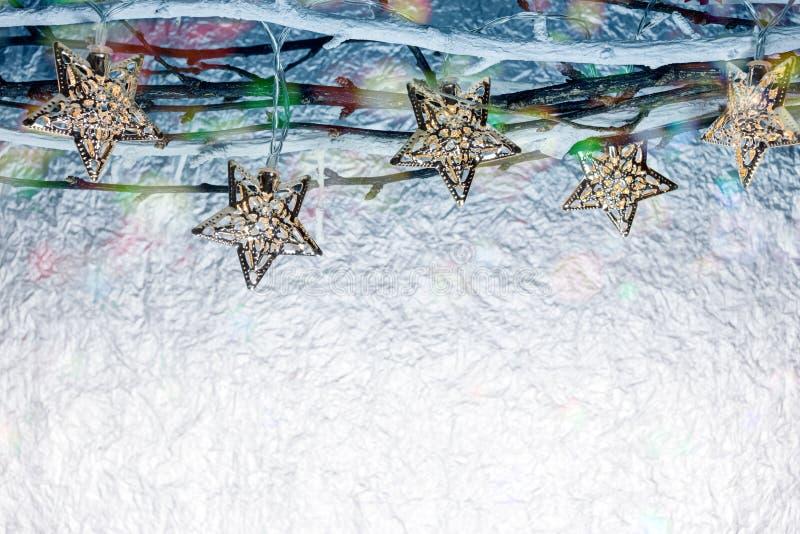 El día de fiesta de la Navidad enciende la ejecución en ramas desnudas contra blurre foto de archivo libre de regalías