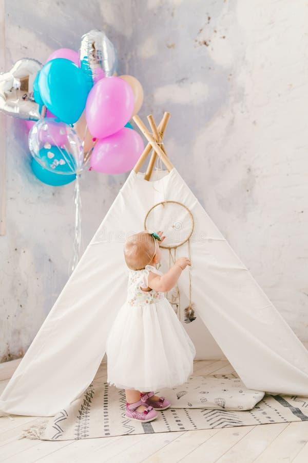 El día de fiesta es el cumpleaños del ` s del niño un año Una muchacha rubia en un vestido está perpetuo dentro del interior en c imagenes de archivo