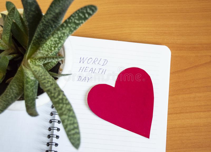 El día de salud de mundo se escribe en un cuaderno, al lado de una flor suculenta viva en un pote y un corazón rojo Imagen concep fotos de archivo