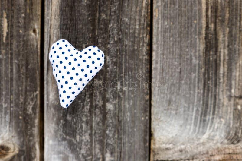 El día de San Valentín, azul punteó el corazón hecho a mano en fondo de madera gris Corazón verde estilizado de la ilustración de fotos de archivo