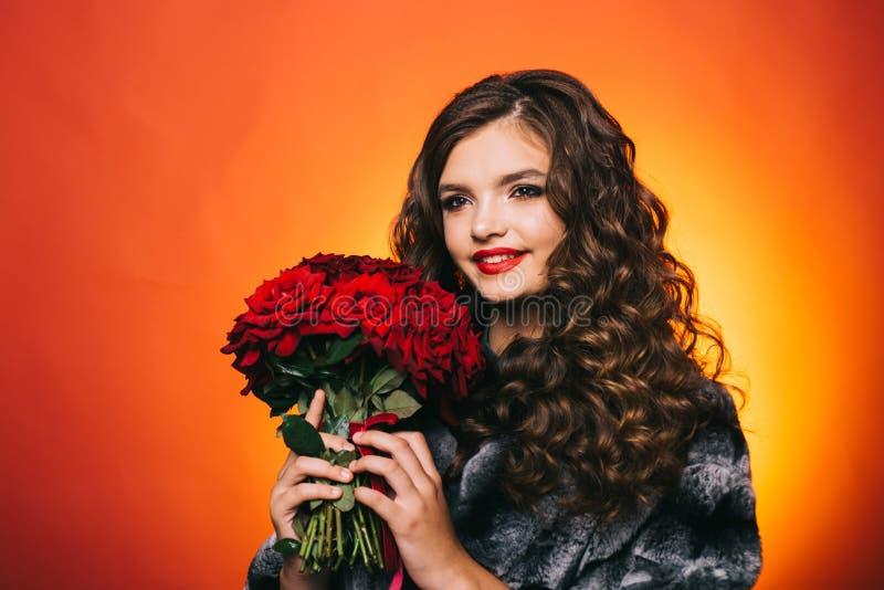 El día de sensaciones y de entusiasmo calientes Sonrisa de la mujer joven con las flores frescas Rosas rojas del control feliz de imagen de archivo