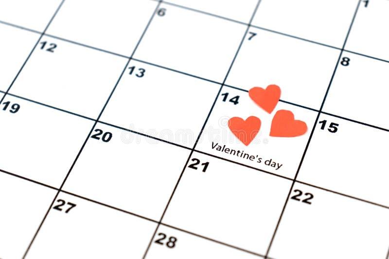 El día de tarjeta del día de San Valentín, el 14 de febrero, en el calendario con los corazones rojos fotos de archivo