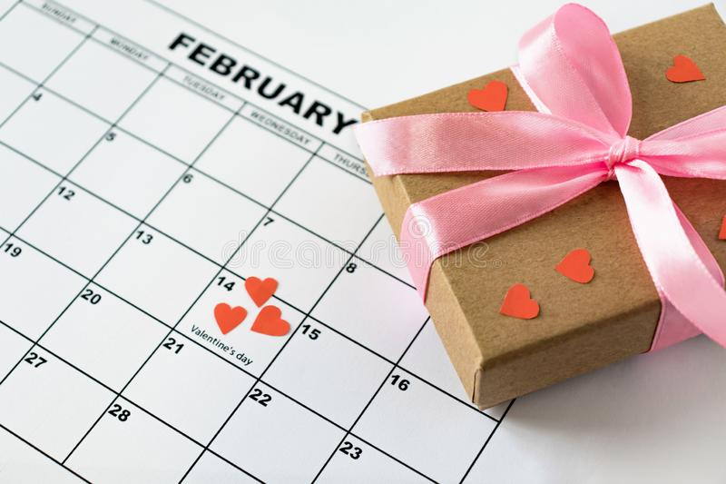 El día de tarjeta del día de San Valentín, el 14 de febrero en el calendario con los corazones y la caja de regalo rojos fotografía de archivo libre de regalías