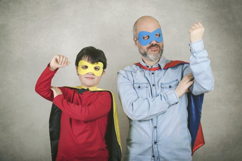 El día, el padre y el hijo de padre vestidos como super héroe fotos de archivo libres de regalías
