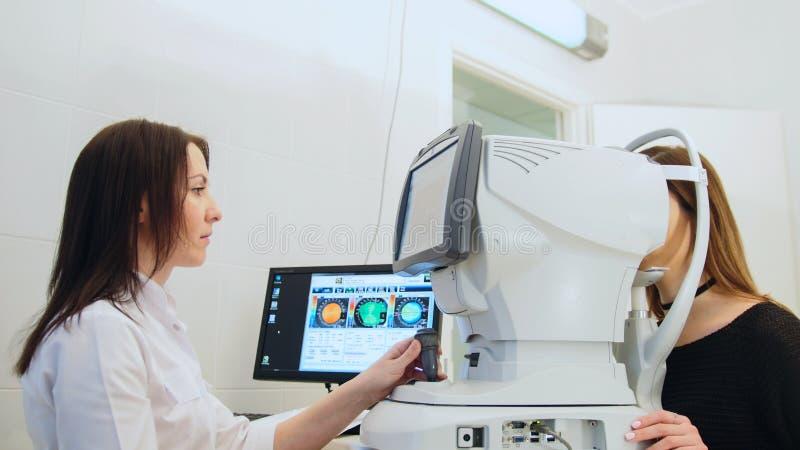El ` de examen s de la mujer del oftalmólogo observa con el equipo de alta tecnología en centro médico imagen de archivo