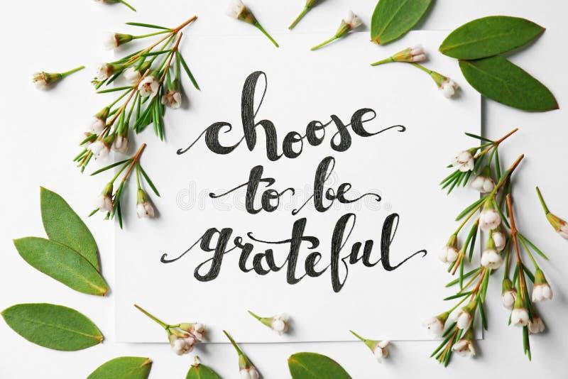 El ` de la cita elige ser ` agradecido escrito en el papel con las hojas y las flores en el fondo blanco imágenes de archivo libres de regalías