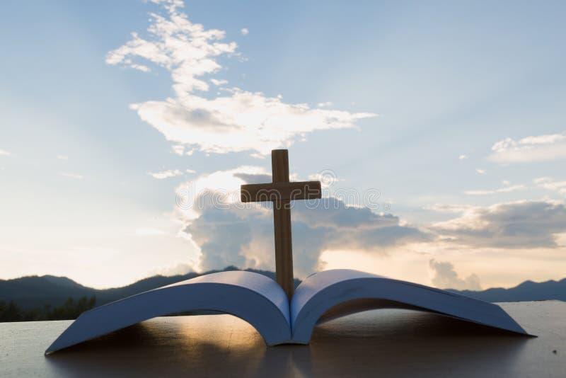 El de madera cruzan la biblia encima abierta en la tabla de madera, fondo hermoso del cielo foto de archivo