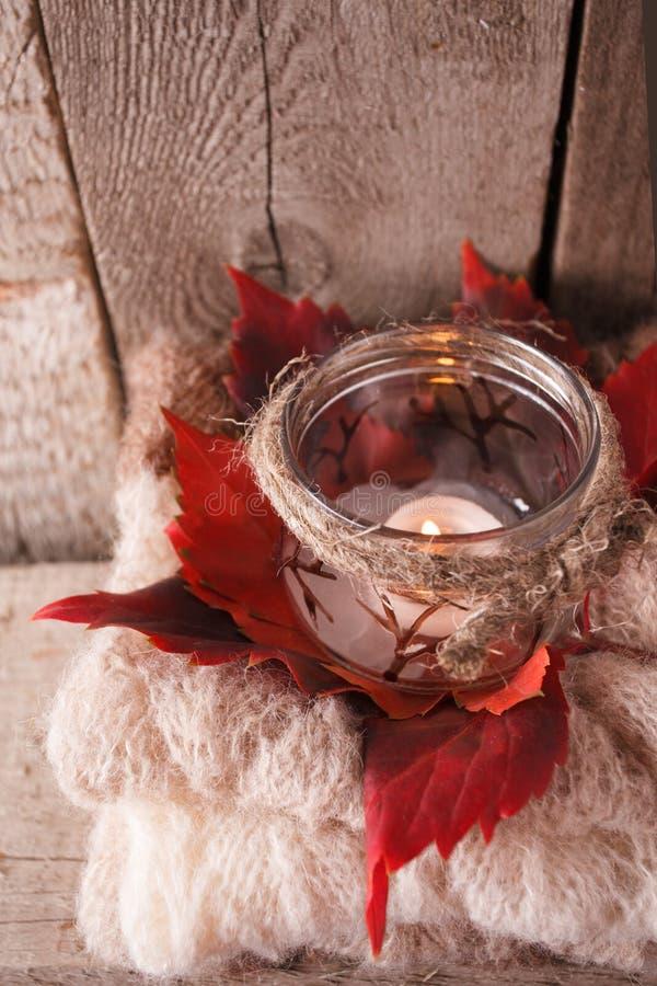 El decoraton rústico con la palmatoria interior hecha a mano y calienta la bufanda hecha punto en el fondo de madera marrón, perf fotografía de archivo