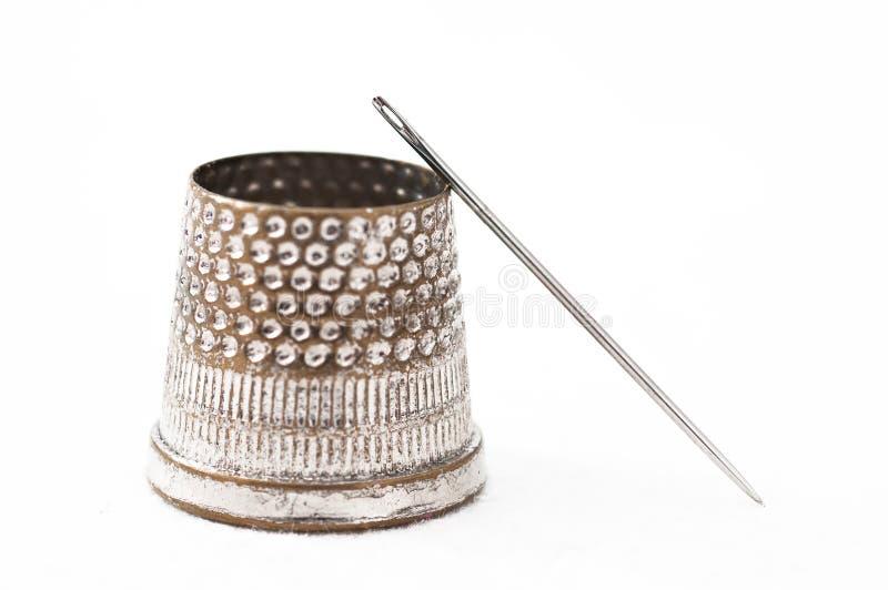 El dedal y la aguja del sastre fotografía de archivo