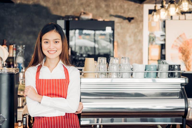 El delantal rojo del desgaste femenino asiático del barista cruzó sus brazos en el contador fotografía de archivo libre de regalías