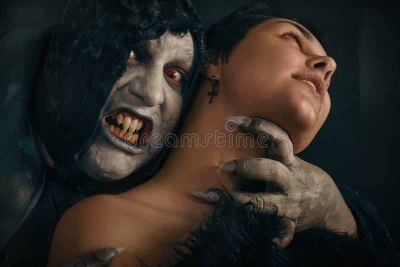 El demonio antiguo del vampiro del monstruo muerde un cuello de la mujer Halloween fant imagenes de archivo