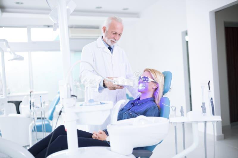 El dentista ajusta los dientes que blanquea el dispositivo fotos de archivo