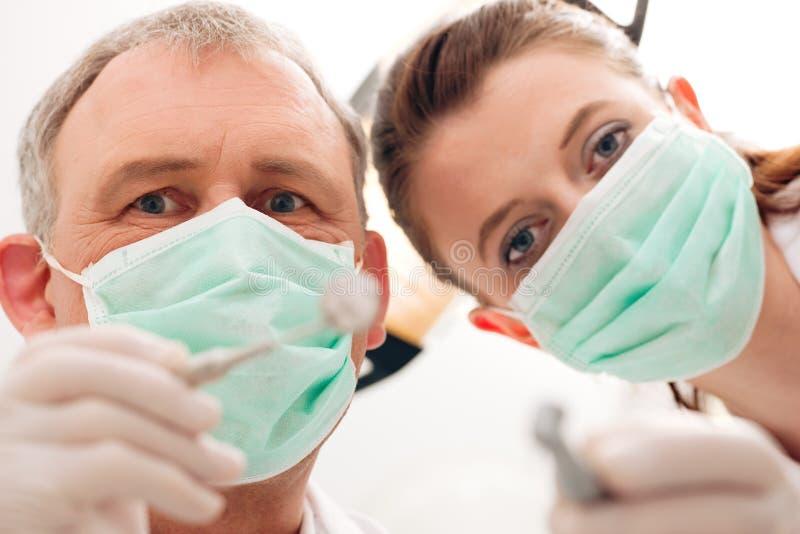 El dentista, auxiliar y perfora adentro un tratamiento foto de archivo