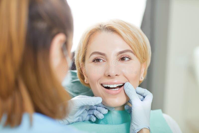 El dentista comprueba el diente de un paciente de la muchacha en una clínica dental imágenes de archivo libres de regalías