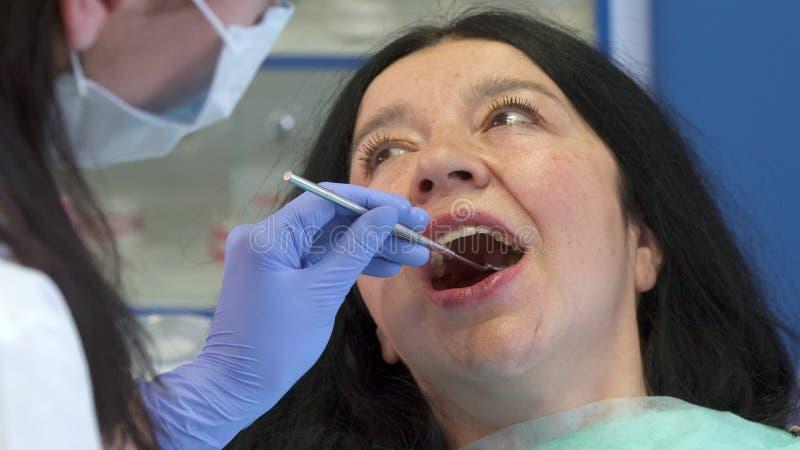El dentista comprueba encima de los dientes del ` s de la mujer imagen de archivo libre de regalías