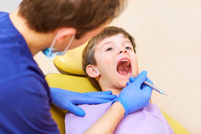 El dentista comprueba los dientes de un adolescente del muchacho del hombre imagen de archivo libre de regalías
