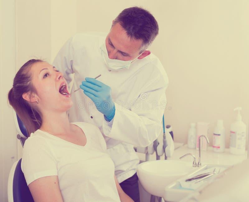 El dentista está tratando al paciente femenino que se está sentando en el ch dental imagen de archivo