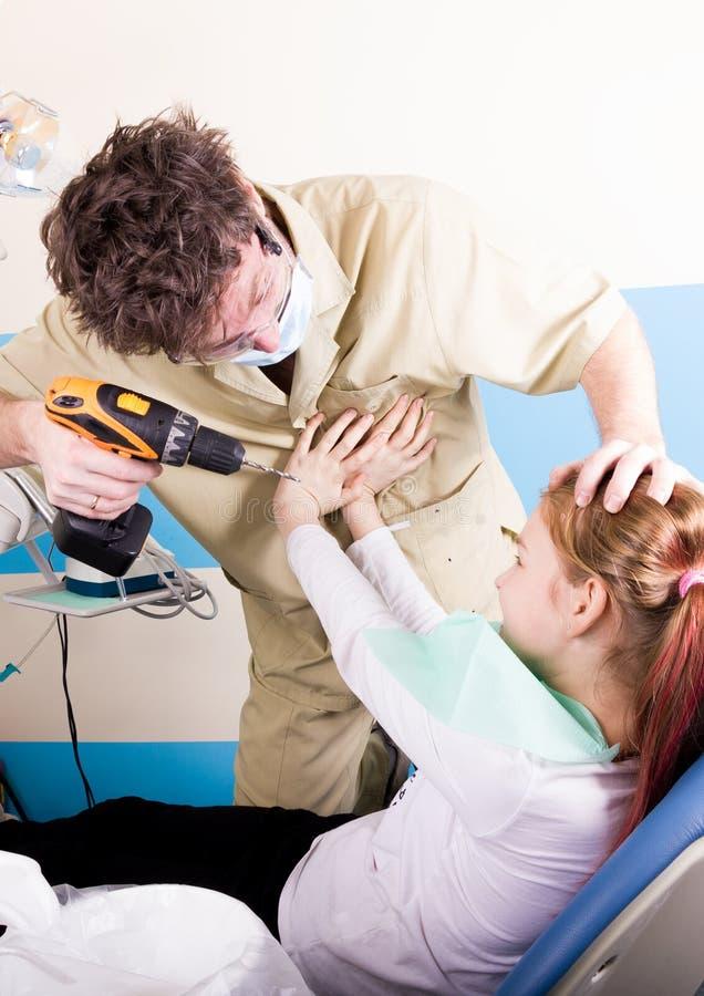 El dentista loco trata los dientes del paciente desafortunado Aterrorizan al paciente foto de archivo libre de regalías