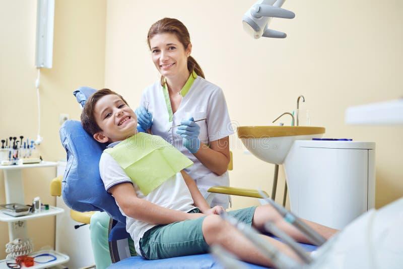 El dentista trata los dientes de un niño a un muchacho en una oficina dental imagenes de archivo