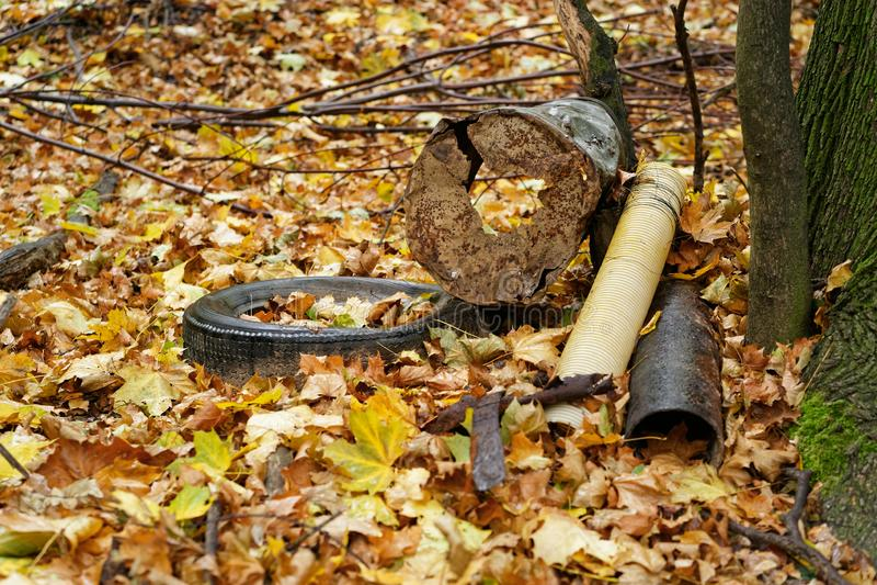 El depósito en el bosque en un árbol, neumáticos de coche, pedazo de metal, componentes, hojas de la basura de otoño cubre la tie imagen de archivo