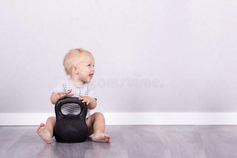 El deporte es vida Niño de risa feliz que se sienta en el piso con el kettlebell Copie el espacio foto de archivo