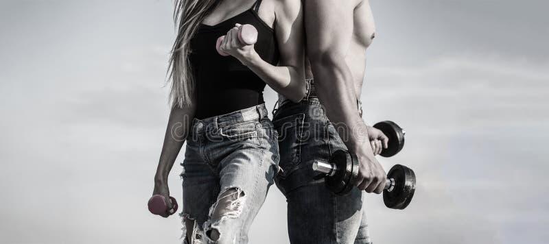 El deporte, pesa de gimnasia, aptitud, par se divierte Mujer y hombre juguetones, equipo Pares atractivos deportivos que muestran imagen de archivo libre de regalías