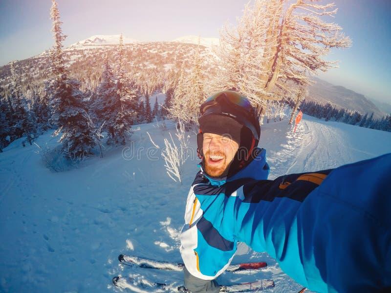 El deportista del individuo de Selfie va en el esquí normal en cuesta del esquí con la cámara de la acción Puesta del sol Inviern foto de archivo