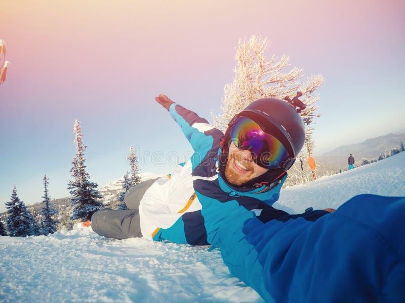 El deportista del individuo de Selfie va en el esquí normal en cuesta del esquí con la cámara de la acción Puesta del sol Inviern imagen de archivo libre de regalías
