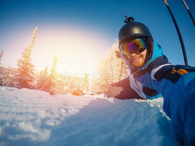 El deportista del individuo de Selfie va en el esquí normal en cuesta del esquí con la cámara de la acción Puesta del sol Inviern imagenes de archivo